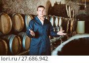 Купить «Man checking ageing barrel process», фото № 27686942, снято 22 сентября 2016 г. (c) Яков Филимонов / Фотобанк Лори