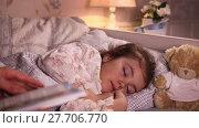 Купить «Mom reading a book while putting her little daughter to sleep», видеоролик № 27706770, снято 18 февраля 2016 г. (c) Алексей Кузнецов / Фотобанк Лори