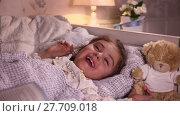 Купить «Little girl laughs while lying in her bed before going to sleep», видеоролик № 27709018, снято 19 февраля 2016 г. (c) Алексей Кузнецов / Фотобанк Лори