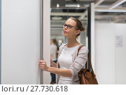Купить «Pretty, young woman choosing the right furniture for her apartment in a modern home furnishings store (color toned image; shallow DOF)», фото № 27730618, снято 21 марта 2019 г. (c) PantherMedia / Фотобанк Лори