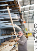 Купить «Man choosing and buying construction wood in a DIY store for his DIY home re-modeling project», фото № 27730670, снято 22 сентября 2018 г. (c) PantherMedia / Фотобанк Лори