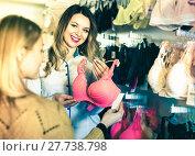 Купить «Female seller demonstrating client bras in underwear store», фото № 27738798, снято 20 марта 2017 г. (c) Яков Филимонов / Фотобанк Лори