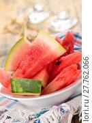 Купить «Closeup shot of fresh sliced watermelon in plate. On rustic wooden table.», фото № 27762066, снято 14 декабря 2018 г. (c) PantherMedia / Фотобанк Лори
