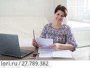 Купить «Woman working with documents looking at laptop», фото № 27789382, снято 21 января 2018 г. (c) Володина Ольга / Фотобанк Лори