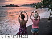 Купить «Girls photographing sunset on beach», фото № 27814262, снято 2 февраля 2018 г. (c) Andriy Bezuglov / Фотобанк Лори