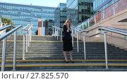 Купить «Business woman standing on the stairs and talking on a cell phone on the background of office building», видеоролик № 27825570, снято 14 июля 2015 г. (c) Алексей Кузнецов / Фотобанк Лори