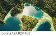 Купить «Coron, Palawan, Philippines, aerial view of beautiful Twin lagoon and limestone cliffs. Fisheye view.», видеоролик № 27828438, снято 5 февраля 2018 г. (c) Mikhail Davidovich / Фотобанк Лори