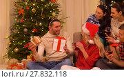 Купить «friends celebrating christmas and giving presents», видеоролик № 27832118, снято 16 января 2018 г. (c) Syda Productions / Фотобанк Лори
