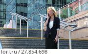 Купить «Business woman standing on the stairs and talking on a cellular phone amid office building», видеоролик № 27854698, снято 14 июля 2015 г. (c) Алексей Кузнецов / Фотобанк Лори