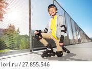 Купить «Happy roller skater posing on floor at skate park», фото № 27855546, снято 14 октября 2017 г. (c) Сергей Новиков / Фотобанк Лори