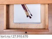 Купить «paint brushes on drawing album in open drawer», фото № 27910670, снято 22 июля 2018 г. (c) PantherMedia / Фотобанк Лори