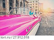 Купить «HAVANA- JANUARY 27, 2013: The beautiful woman at a wheel old American retro car (50th years of the last century), an iconic sight in the city, on the Malecon street, toning», фото № 27912018, снято 27 января 2013 г. (c) Куликов Константин / Фотобанк Лори