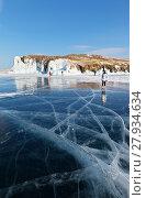 Купить «Baikal Lake in winter sunny cold day. Tourists travel on the ice of a frozen lake near the icy rocks of Olkhon Island», фото № 27934634, снято 11 февраля 2018 г. (c) Виктория Катьянова / Фотобанк Лори