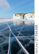 Купить «Beautiful winter landscape of the frozen Lake Baikal in February sunny afternoon. Blue clear ice with lines of cracks and reflection of coastal icy rocks of Olkhon Island», фото № 27934698, снято 11 февраля 2018 г. (c) Виктория Катьянова / Фотобанк Лори