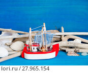 Купить «Toy sailboat, weathered wood and seashells on blue wood», фото № 27965154, снято 27 марта 2019 г. (c) PantherMedia / Фотобанк Лори