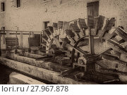 Купить «Old wheels of a watermill. Vintage style picture. Adding grain to give an old photo effect.», фото № 27967878, снято 23 марта 2019 г. (c) PantherMedia / Фотобанк Лори