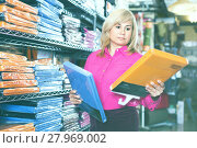 Купить «Mature female customer choosing color bedsheet in textile store», фото № 27969002, снято 17 января 2018 г. (c) Яков Филимонов / Фотобанк Лори