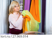 Купить «Mature woman seller showing curtain in the curtains shop», фото № 27969014, снято 17 января 2018 г. (c) Яков Филимонов / Фотобанк Лори