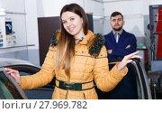 Купить «Smiling female is satisfied of tire winter replacement of her car», фото № 27969782, снято 18 декабря 2017 г. (c) Яков Филимонов / Фотобанк Лори