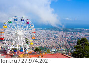 BARCELONA, SPAIN - JULY 13, 2016:Ferris wheel in Tibidabo with panoramic view over Barcelona. It is located at free access area of Tibidabo Amusement Park. Редакционное фото, фотограф Papoyan Irina / Фотобанк Лори