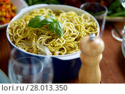 Купить «pasta with basil in bowl and other food on table», фото № 28013350, снято 5 октября 2017 г. (c) Syda Productions / Фотобанк Лори