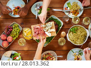Купить «group of people eating at table with food», фото № 28013362, снято 5 октября 2017 г. (c) Syda Productions / Фотобанк Лори