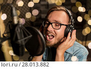 Купить «man with headphones singing at recording studio», фото № 28013882, снято 18 августа 2016 г. (c) Syda Productions / Фотобанк Лори