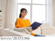 Купить «young asian woman in glasses reading book at home», фото № 28013966, снято 9 марта 2016 г. (c) Syda Productions / Фотобанк Лори
