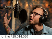 Купить «man with headphones singing at recording studio», фото № 28014030, снято 18 августа 2016 г. (c) Syda Productions / Фотобанк Лори