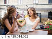 Купить «happy young women drinking coffee at outdoor cafe», фото № 28014062, снято 9 августа 2015 г. (c) Syda Productions / Фотобанк Лори