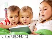 little kids with tablet pc in bed at home. Стоковое фото, фотограф Syda Productions / Фотобанк Лори