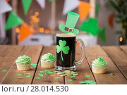 Купить «shamrock on glass of beer, green cupcakes and coins», фото № 28014530, снято 31 января 2018 г. (c) Syda Productions / Фотобанк Лори