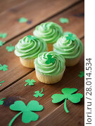 Купить «green cupcakes with shamrock decorations on table», фото № 28014534, снято 31 января 2018 г. (c) Syda Productions / Фотобанк Лори