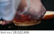 Chef preparing the burger, frying the bun on the grill, putting the tomatoes. Стоковое видео, видеограф Константин Шишкин / Фотобанк Лори
