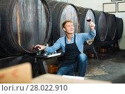 Купить «man with glass of wine in wine cellar», фото № 28022910, снято 23 июля 2018 г. (c) Яков Филимонов / Фотобанк Лори