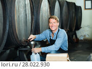 Купить «friendly man working in winery pouring wine from wood to plastic bottle in cellar», фото № 28022930, снято 20 октября 2018 г. (c) Яков Филимонов / Фотобанк Лори