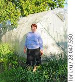 Купить «Пожилая женщина стоит около теплицы», эксклюзивное фото № 28047550, снято 18 июня 2010 г. (c) Юрий Морозов / Фотобанк Лори
