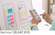 Купить «woman working on smartphone interface design», видеоролик № 28047810, снято 10 февраля 2018 г. (c) Syda Productions / Фотобанк Лори