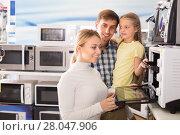 Купить «Portrait of positive family choosing microwave», фото № 28047906, снято 22 августа 2018 г. (c) Яков Филимонов / Фотобанк Лори