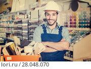Купить «Smiling guy painter with folded arms in paint shop», фото № 28048070, снято 13 сентября 2017 г. (c) Яков Филимонов / Фотобанк Лори