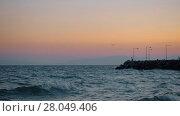 Купить «Evening waterscape with wavy sea, rocky pier and flying gull», видеоролик № 28049406, снято 5 июня 2020 г. (c) Данил Руденко / Фотобанк Лори
