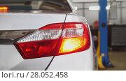 Купить «Auto service - checking back headlights of car», фото № 28052458, снято 23 мая 2018 г. (c) Константин Шишкин / Фотобанк Лори