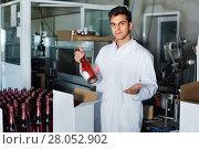 Купить «Man standing in packing section on winemaking factory», фото № 28052902, снято 21 сентября 2016 г. (c) Яков Филимонов / Фотобанк Лори