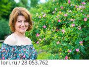 Купить «Portrait of beautiful woman on background of a blossoming wild rose», фото № 28053762, снято 19 июня 2017 г. (c) Володина Ольга / Фотобанк Лори