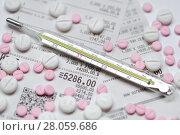 Купить «Рассыпанные таблетки и градусник на фоне аптечных чеков», фото № 28059686, снято 2 января 2018 г. (c) Роман Рожков / Фотобанк Лори