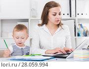 Купить «Woman is working on laptop while kid painting on papers», фото № 28059994, снято 13 июня 2017 г. (c) Яков Филимонов / Фотобанк Лори