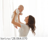 Mom holds a baby in the arms window background. Стоковое фото, фотограф Ekaterina Demidova / Фотобанк Лори