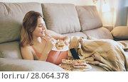 Купить «Positive woman on sofa with fresh cake and remote watching tv», видеоролик № 28064378, снято 18 октября 2017 г. (c) Яков Филимонов / Фотобанк Лори