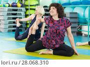 Купить «Women doing yoga exercise in the gym», фото № 28068310, снято 18 февраля 2018 г. (c) Владимир Мельников / Фотобанк Лори