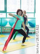 Купить «Women doing gym exercises using latex fitness bands», фото № 28072822, снято 18 февраля 2018 г. (c) Владимир Мельников / Фотобанк Лори